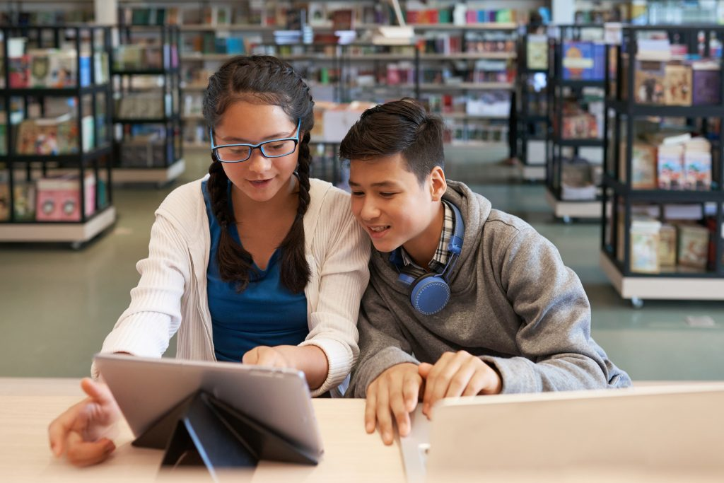 Little girl and boy surfing tablet while sitting at table in school library and smiling