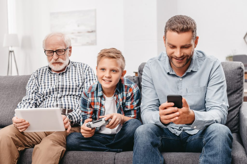 Father, son and grandfather sitting together on couch in living room using various digital devices
