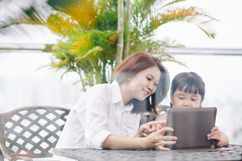 Young mother spending time with daughter in cafe and helping her to upload new application on digital tablet