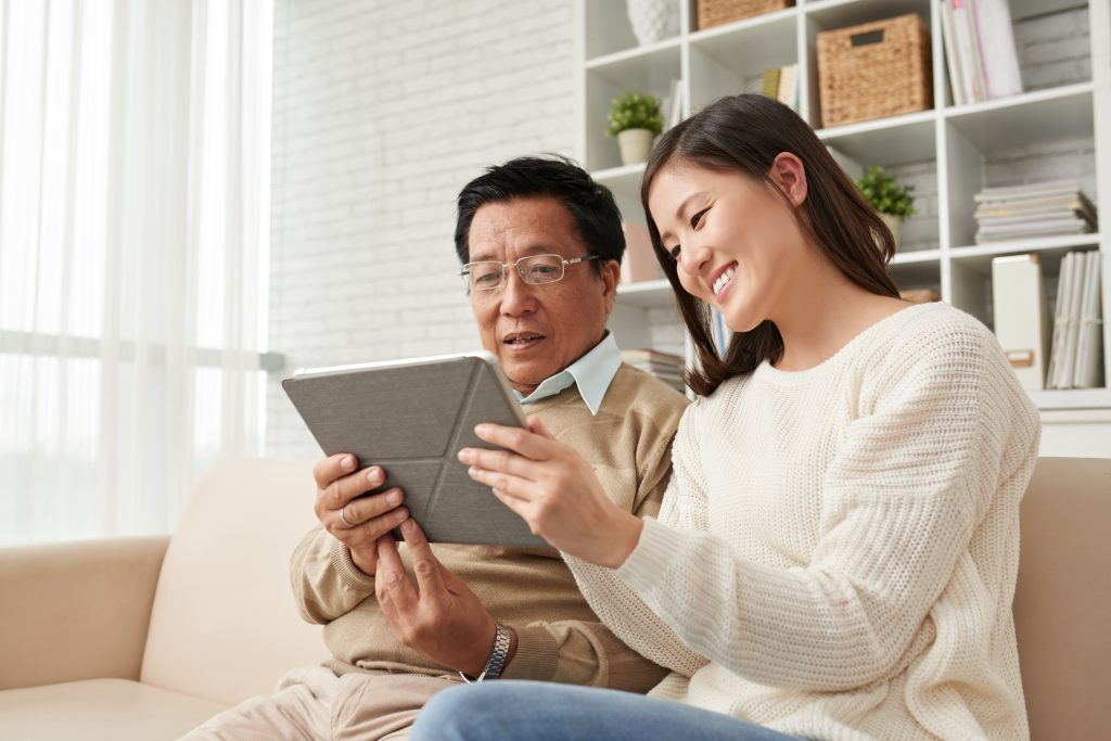 Joyful Asian woman sitting on sofa with her senior dad and explaining him how to play computer game on digital tablet