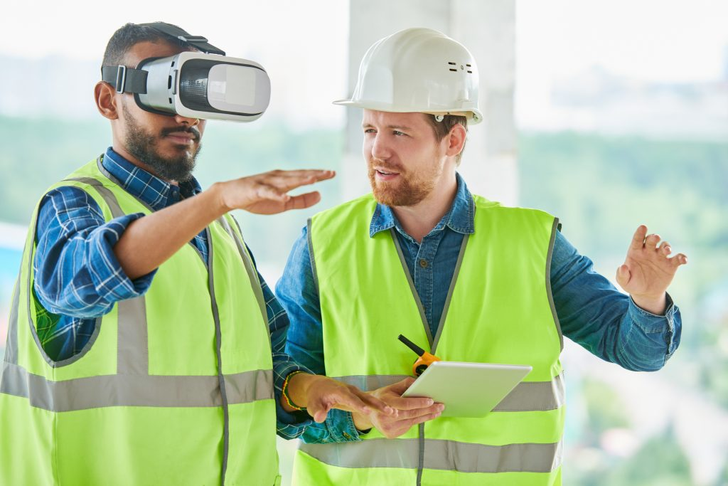Concentrated handsome mixed race engineer with beard gesturing while using VR simulator for building visualization, his colleague explaining project to him