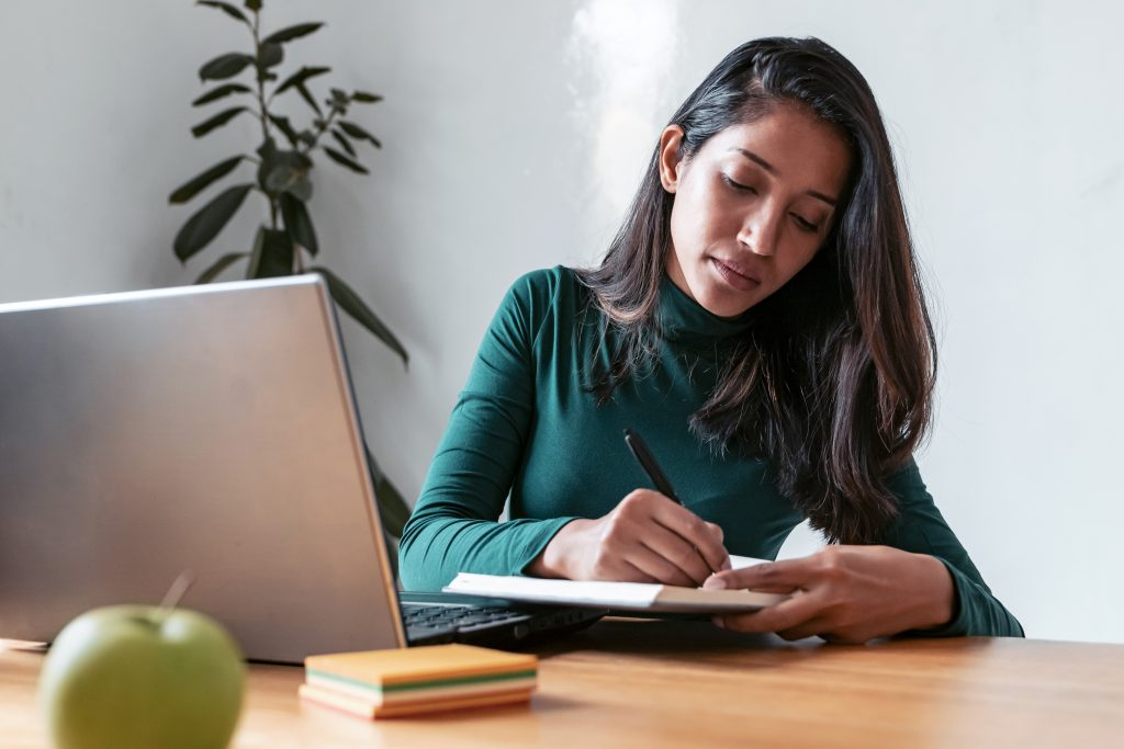 Shot of young indian business woman entrepreneur writing in her agenda while working with laptop in the office.